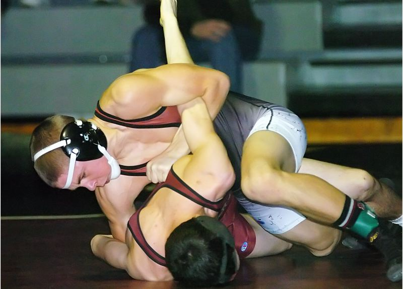 by: DAN BROOD - TURNING HIM -- Sherwood sophomore Jess Hatfield (top) looks to turn Milwaukie's Zander Carlson during their 132-pound match at last week's dual meet. Hatfield and the Bowmen came away with wins.