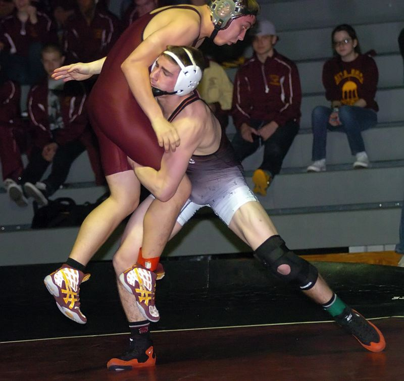 by: DAN BROOD - GOING UP -- Sherwood senior Nic Clarke (right) lifts Milwaukie's Alex Elmore during their 152-pound match.