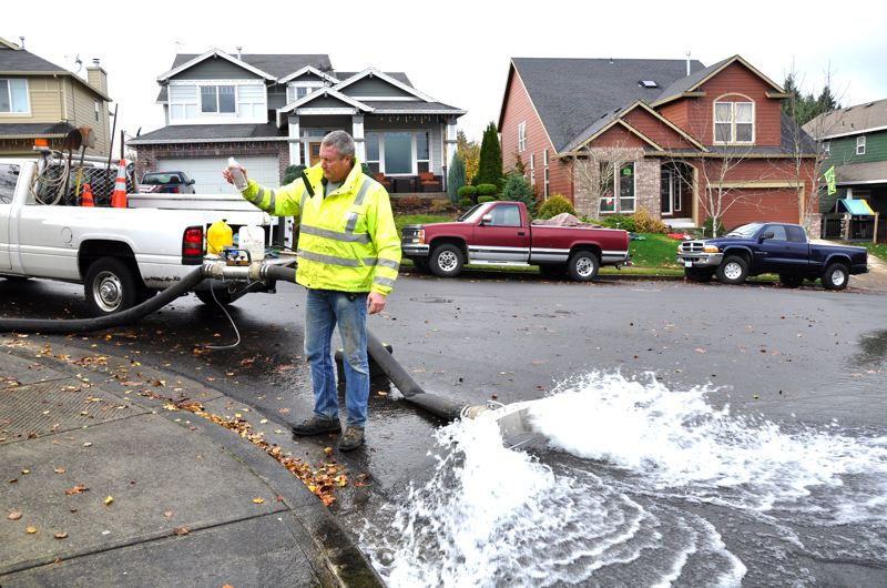 by: CITY OF GRESHAM: TAM DRISCOLL - Scott Griffin, water distribution technician for the City of Gresham, checks a bottle of water for clarity while flushing from a hydrant. Technicians don't stop flushing the water until it is crystal clear.