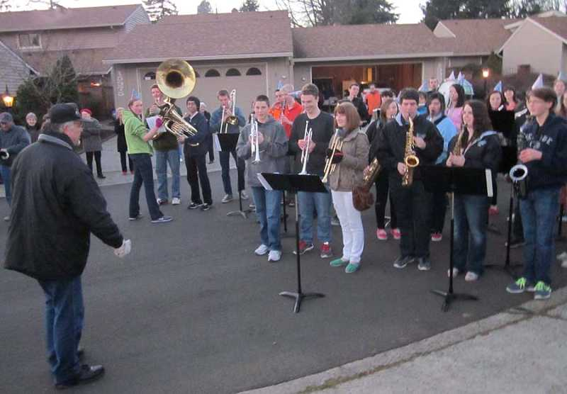 by: BARBARA SHERMAN - PERFORMANCE ON OAKTREE LANE - About half of the Tigard High School marching band, led by director Jim Irving (left), showed up in Summerfield to play 'Happy Birthday' and some patriotic songs outside the home of Army Air Corps veteran Marion Hill on Jan. 18 at the request of his family.