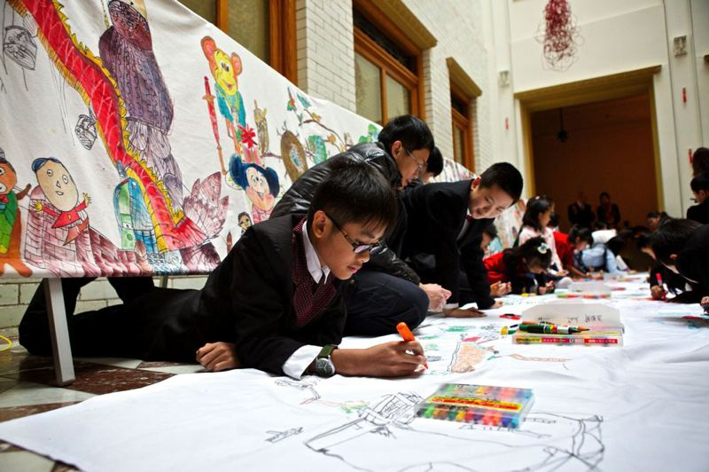by: TRIBUNE PHOTO: JAIME VALDEZ - Chen Junlong, 13, from China paints a scene from his memory of his visit in Portland during Friday's Year of the Horse celebration at City Hall.