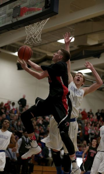 Lincoln's Tim Graham goes for a reverse layup, as Grant's Deiondre Bird tries to challenge  the move.