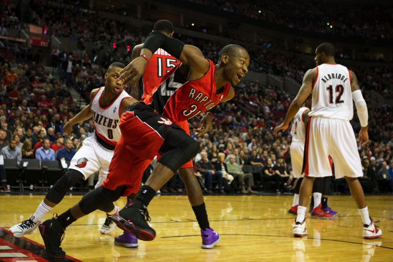 by: TRIBUNE PHOTO: JAIME VALDEZ - Terrence Ross, Toronto Raptors guard from Jefferson High, runs around a screen as the Trail Blazers' Damian Lillard gives chase Saturday  night at Moda Center.
