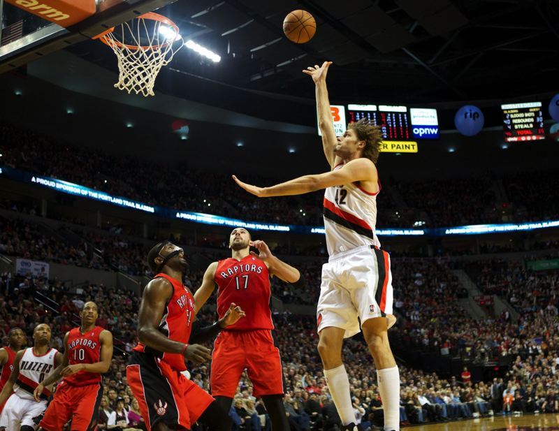 by: TRIBUNE PHOTO: JAIME VALDEZ - Blazers center Robin Lopez shoots over Raptors power forward Patrick Patterson (54) and center Jonas Valanciunas (17).