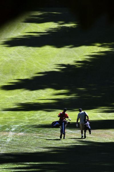 by: TRIBUNE FILE PHOTO: JIM CLARK - Two golfers walk one of the tree-lined holes at Glendoveer.