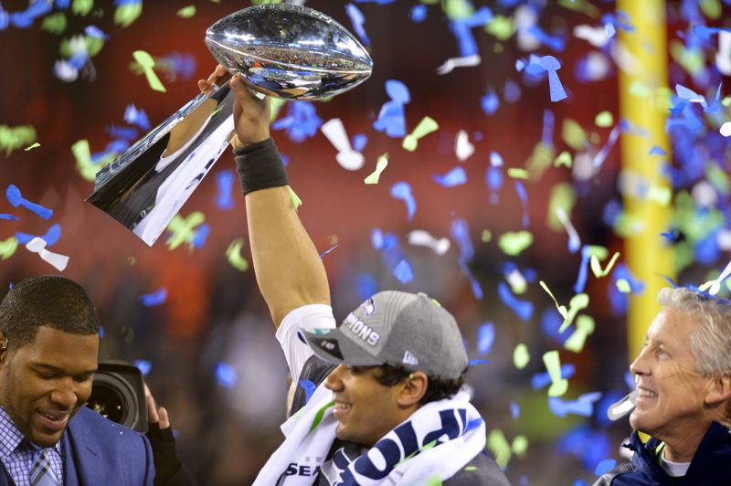 Seattle quarterback Russell Wilson shows off the Vince Lombardi Trophy on stage with Seahawks coach Pete Carroll (right) after Super Bowl XLVII.