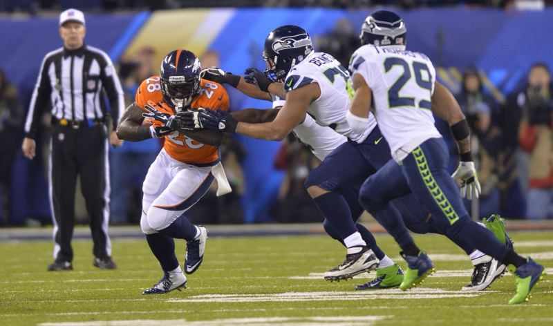 Seattle linebacker Michael Bennett and safety Earl Thomas move in to bring down Denver running back Montee Ball.