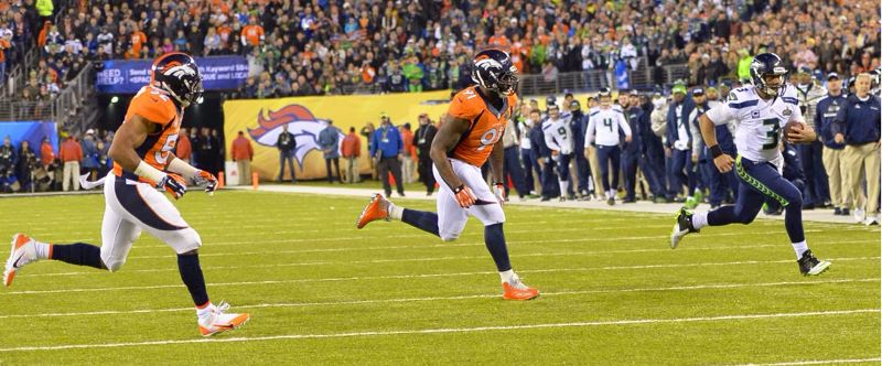 A scampering Russell Wilson eludes the Broncos' defense.