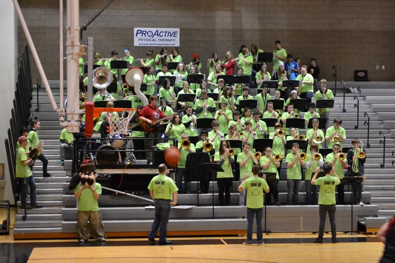 by: PHOTO COURTESY: CHRISTY PARRISH - Oregon City High School's Pioneer Pep Band, which is the sixth man at OC basketball games, is currently wearing bright green for a senior band member fighting lymphoma.