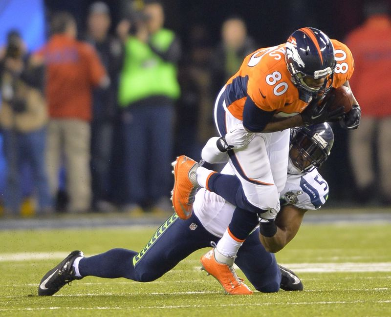 Julius Thomas, Denver's tight end from Portland State, is dragged down by Seattle linebacker Bobby Wagner. Thomas had four catches for 27 yards.