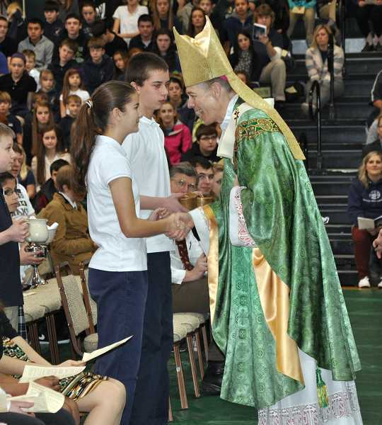 by: SUBMITTED - Archbishop Alexander Sample greets Sacred Heart eighth-grade students Natali Herinckx and Cole Olheiser.