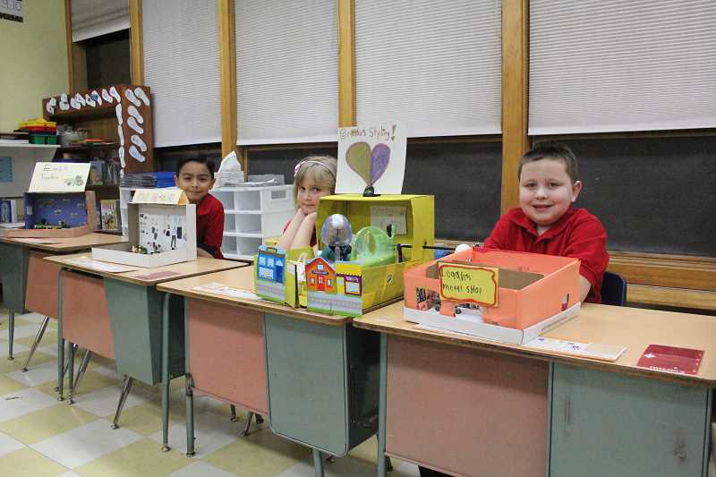 by: MAYGAN BECKERS - Emmanuel Sandoval, Brooke Haase and Logan Kirsch wait to share their 'working world' projects with parents in Katie Stuart's second grade classroom.