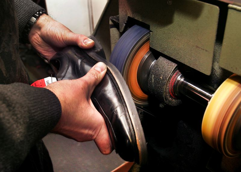 by: OUTLOOK PHOTO: JIM CLARK - Shoe repairman Gene Norman grinds the sole of a dress shoe in his downtown Gresham store.
