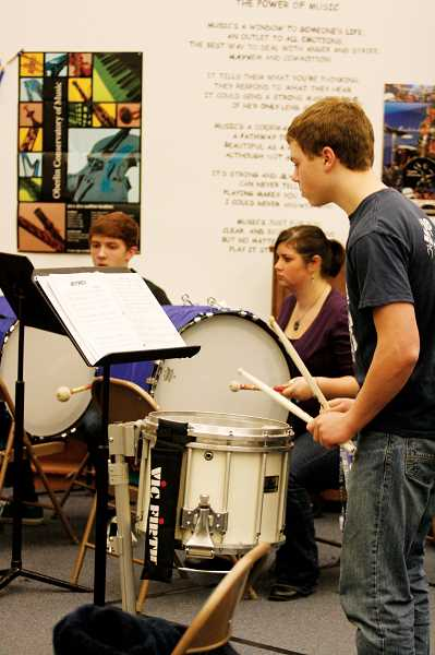 by: PHIL HAWKINS - David Wright takes a stab at the snares during a Friday practice while Kyle Kinyon and music teacher Kalyn Hanna play bass.