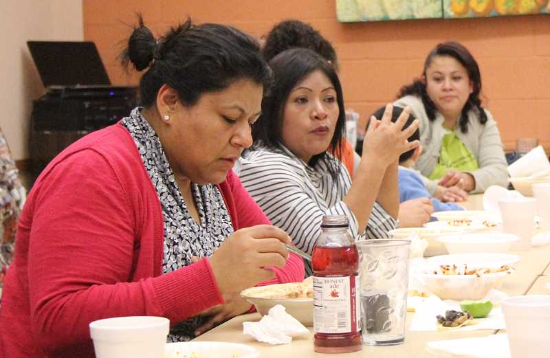 by: MAYGAN BECKERS - (Left) Brenda Mendoza, vice president of PCUN and director of service center for farmworkers, and Carmen Dejesus, share a conversation while they eat their first meal after 24 hours of fasting for immigration reform awareness.