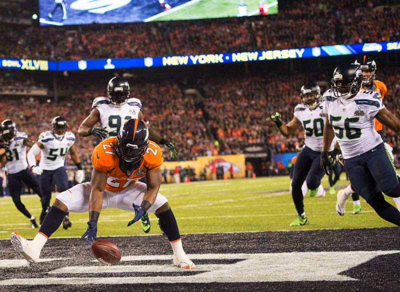 Knowshon Moreno recovers the ball in the end zone for a safety, as the Seahawks surround him and Broncos quarterback Peyton Manning looks on.