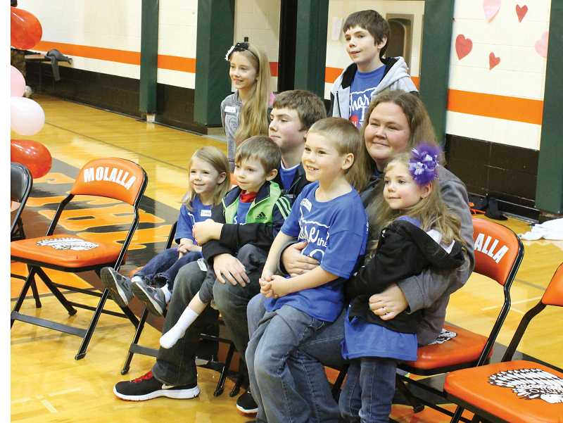 by: CORY MIMMS - The Riehl family shares their love following the Molalla High School Share the Love kick-off assembly Friday, in which Naysen Riehl, 4, was named this year's recipient of the annual fundraiser. Pictured from left, standing: Harliegh, 8 and Manden, 13, Sitting: Kiya, 5, and Naysen, 4, held by Jonathan, 14, Liam, 7, and Ireland, 6, held by their mother, Crystal Riehl, of Molalla.