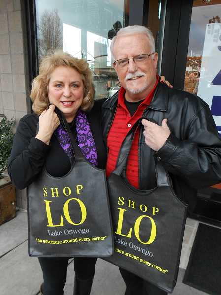by: CLIFF NEWELL - Carol Winston and John Hanan display the shopping bags they hope will help increase shopping in downtown Lake Oswego and Lake Grove.