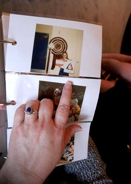 by: TIMES PHOTO: JONATHAN HOUSE - Carol Huckaby goes through an album of photos showing her time with Camp Fire USA when she was a little girl.