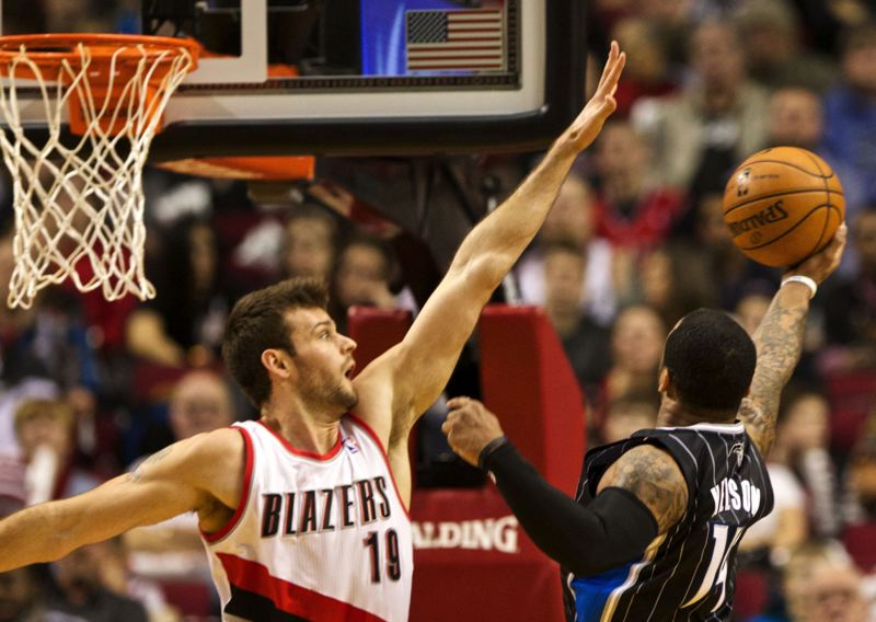 by: TRIBUNE PHOTO: JAIME VALDEZ - Joel Freeland of the Trail Blazers defends Orlando Magic point guard Jameer Nelson.