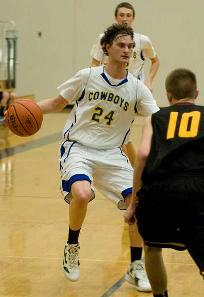 by: LON AUSTIN/CENTRAL OREGONIAN - Andrew Sofich brings the ball down the court on a fast break. Sofich finished with six points and 11 rebounds as the Cowboys lost a close 45-43 game to the Redmond Panthers.