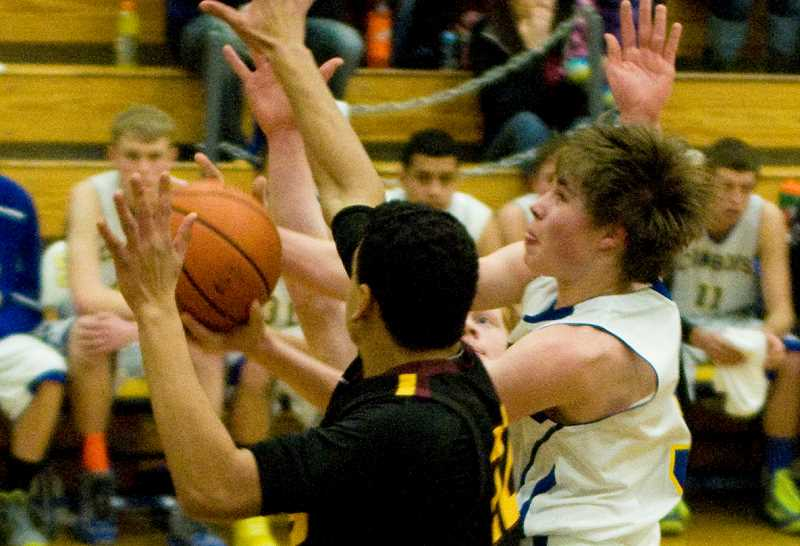 by: LON AUSTIN/CENTRAL OREGONIAN - Blake Bartels is fouled on his way to the basket during the Cowboys' loss to the Redmond Panthers. Bartels led all scorers with 17 points.