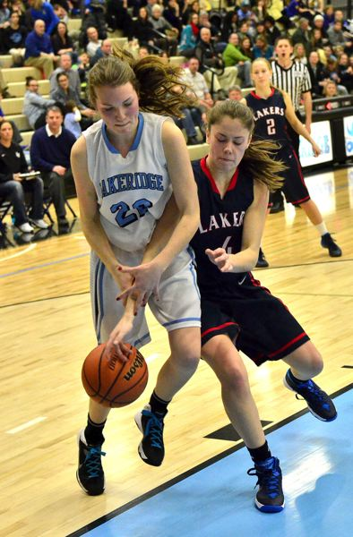by: VERN UYETAKE - Lakeridge's Avery Dauphinais and Lake Oswego's Hannah Plott battle for the ball in the Pacers' victory at home Tuesday.