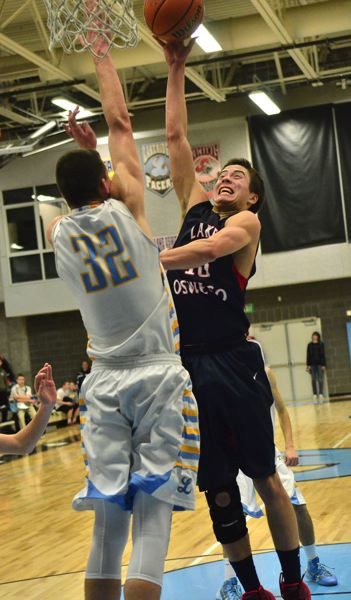 by: VERN UYETAKE - Lake Oswego's Zach Parker looks to lift a shot over Lakeridge's Jake Spurgeon in Tuesday's come-from-behind victory over the Pacers.