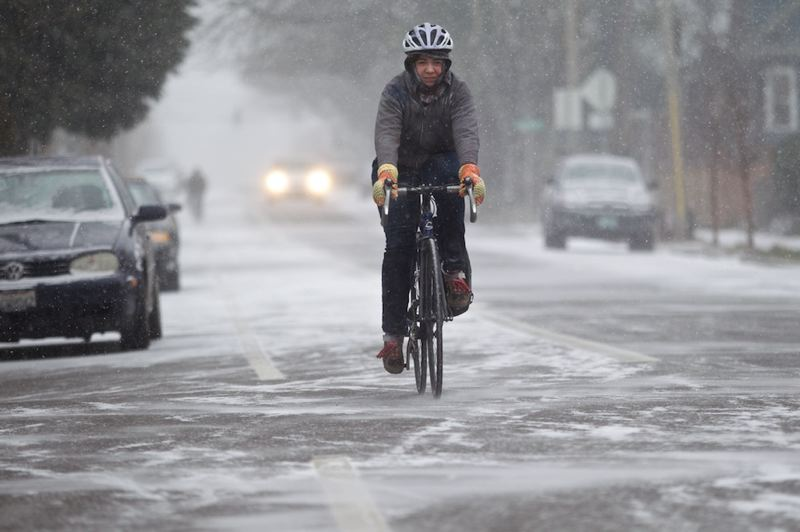 by: TRIBUNE PHOTO: JAIME VALDEZ - A bicyclist rides south on North Vancouver Avenue as snow begins to fall in Portland Thursday morning.