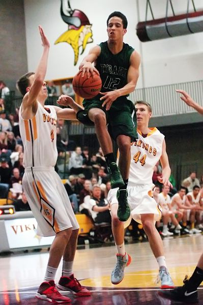 by: DAN BROOD - WALKING ON AIR -- Tigard High School senior Elijah Simon (12) floats toward the basket between Forest Grove's Jalen Hall (left) and Andrew O'Donnell in Friday's game. Simon scored 22 points in the Tigers' win.