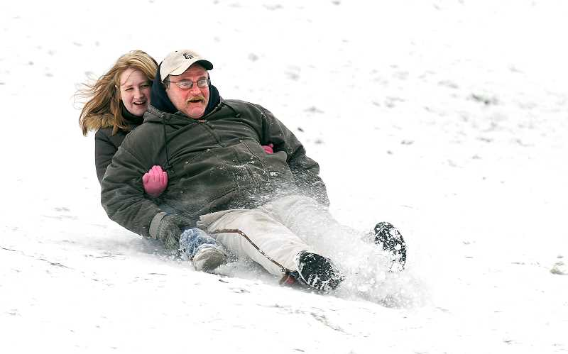 by: GARY ALLEN - Jeff and Cassie Jenks of Newberg enjoy a sled ride down a popular hill at Hoover Park Friday morning.