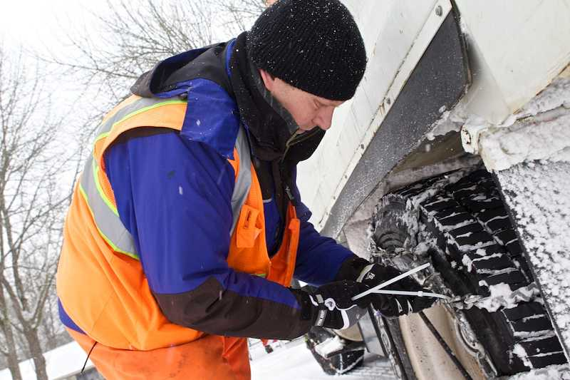 by: JAIME VALDEZ - Tigard Public Works employee Cale Brown uses a zip tie to cinch down the chains on a snow plow he operates. More snow is expected into Saturday, and snow plows will be working around the clock to keep roads as clear as possible.