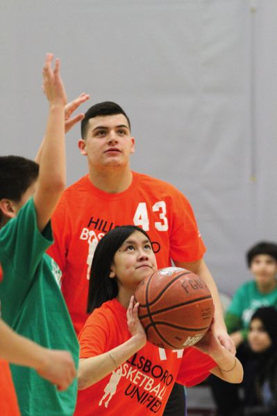 by: HILLSBORO TRIBUNE PHOTO: AMANDA MILES - Kevin Garcia (43) looks on while NgocLan Nguyen takes a shot during the Unified Sports Basketball Invitational on Saturday at Forest Grove High.