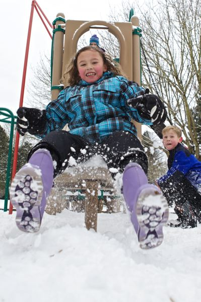 by: PAMPLIN MEDIA GROUP PHOTO: JAIME VALDEZ - Talia Valdez,8, slides down a slide in the snow at River Fox Park in Wilsonville.