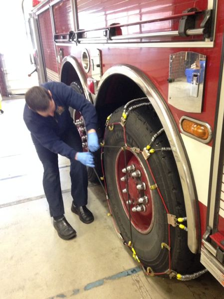 by: PHOTO COURTESY OF: TVF&R - A Tualatin Valley Fire and Rescue firefighter helps put chains on one of the agency's fire engines during last weekend's snow storm.