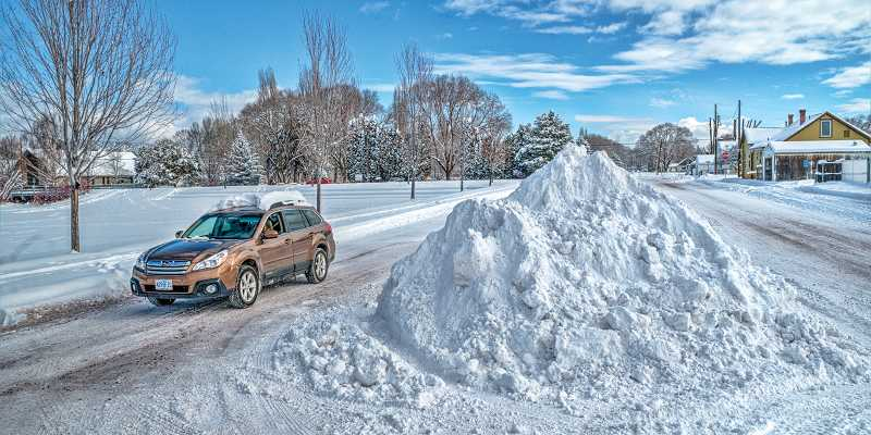 by: LON AUSTIN - A vehicle drives past a mound of plowed snow on Sunday morning following the storm.
