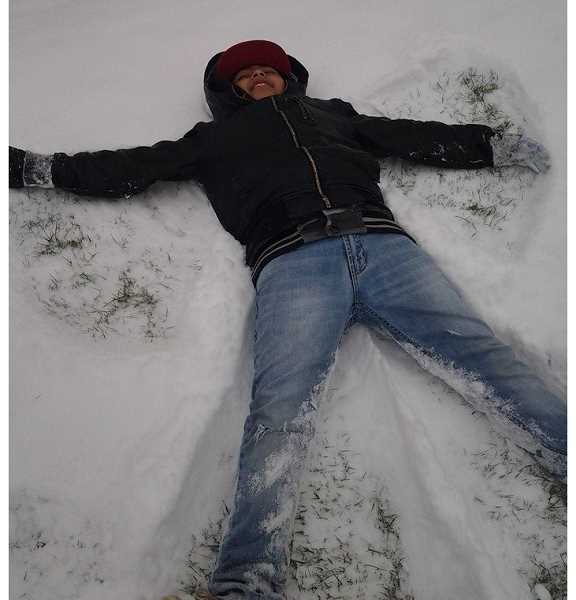by: DINA LOPEZ - Diego Enriquez Lopez, 10, of Woodburn, makes a snow angel outside his home on Friday. Local children were thrilled that school was canceled, while adults struggled to make it to work.