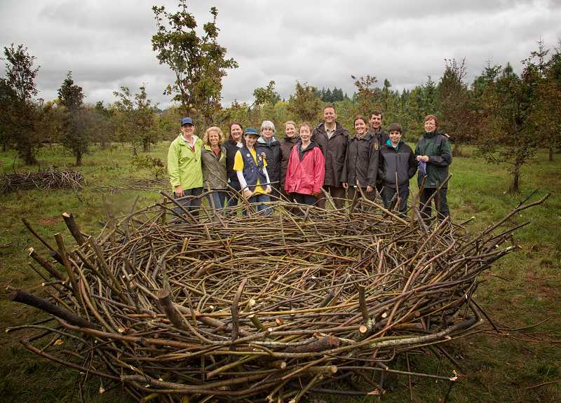 by: BJORN FREDRICKSON - Members of the Friends of the Tualatin River National Wildlife Refuge (along with U.S. Fish and Wildlife staff) in pouring rain following the completion of building an eagle's nest sculpture to symbolize the friends group. The refuge has a several eagles that can often be observed.