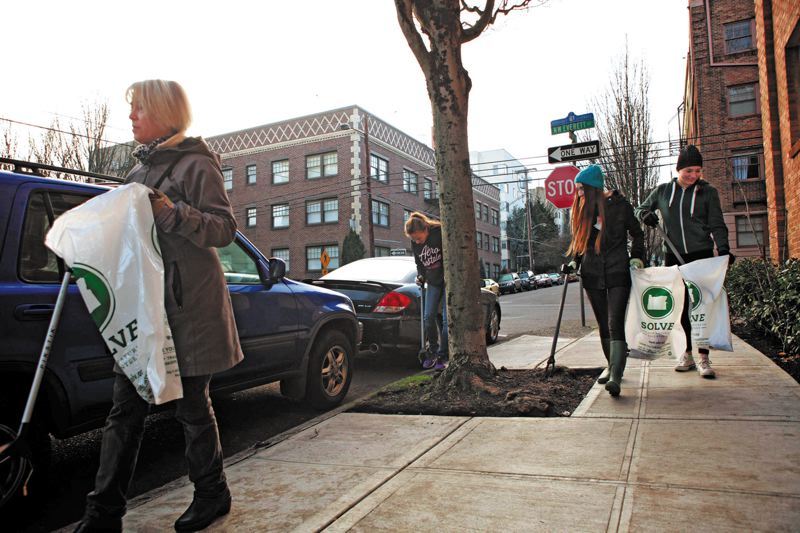 by: TRIBUNE PHOTO: JAIME VALDEZ - Lisa Hamilton, left, leads middle school students Lilly Kennedy, Ruby McShane and Hannah Kennedy  in picking up rubbish in Northwest Portland during a recent SOLVE event.