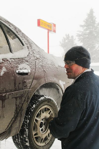 by: NEWS-TIMES PHOTO: JOHN SCHRAG - Joel Vandyke and his co-workers at Les Schwab Forest Grove Tire Cetner were busy Friday installing snow tires and selling chains.