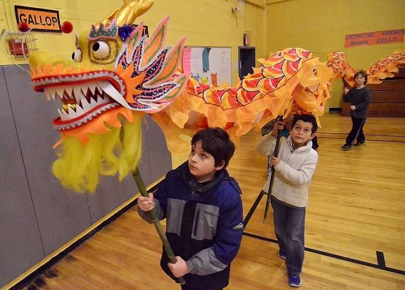 by: TIDINGS PHOTO: VERN UYETAKE - Giovanni Romano, front, and his younger brother, Dominic, help carry Sunsets new Chinese dragon on a parade around the school gym.
