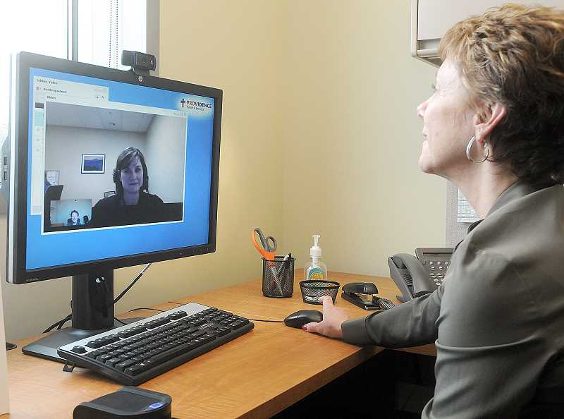 by: SETH GORDON - A more personal approach - Providence Newberg Cancer Clinic director Marlene Sisson speaks with St. Vincent's oncology social worker Erin Leake via the TeleHealth video conferencing pilot program, which provides patients a more personal link to services not available on site in Newberg.