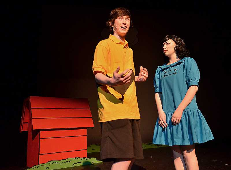 by: REVIEW PHOTO: VERN UYETAKE - Jordan Clarke (Charlie Brown) and Caroline Haroldson (Lucy) practice a scene near Snoopys doghouse.
