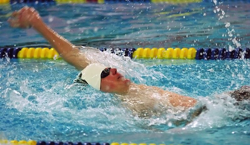 by: DAN BROOD - BACK AT IT -- Tigard High School junior Jacob Morris competes in the 100-yard backstroke event during Tuesday's Pacific Conference dual meet at Newberg. The conference's district meet is set for Friday and Saturday in McMinnville.