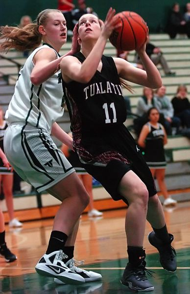 by: DAN BROOD - IN THE PAINT -- Tualatin sophomore Hannah Self (right) looks to go up to the basket against Tigard sophomore Elise Conroy in Wednesday's game.