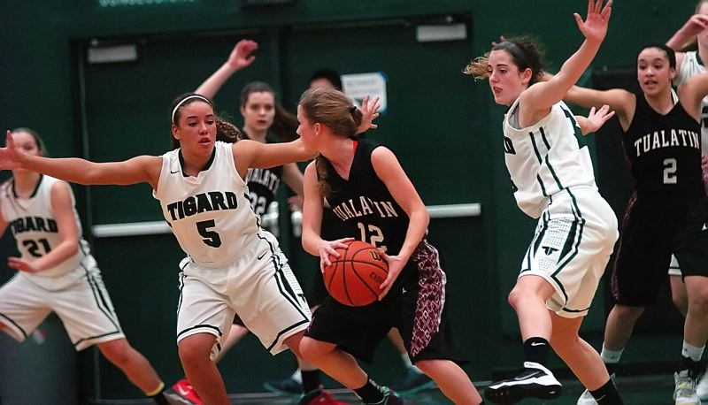 by: DAN BROOD - SWARMING -- Tigard seniors Lexi Carter (5) and Emilee Cincotta keep pressure on Tualatin senior Madi Hall in Wednesday's contest. Carter and Cincotta combined to score 37 points in the Tigers' 62-56 win.