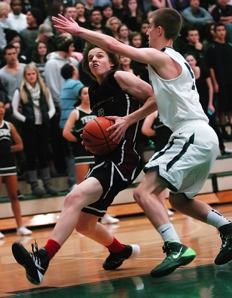 by: DAN BROOD - ON THE MOVE -- Tualatin sophomore Nathan Senger (left) looks to drive to the basket against Tigard senior Nick Kaelin.