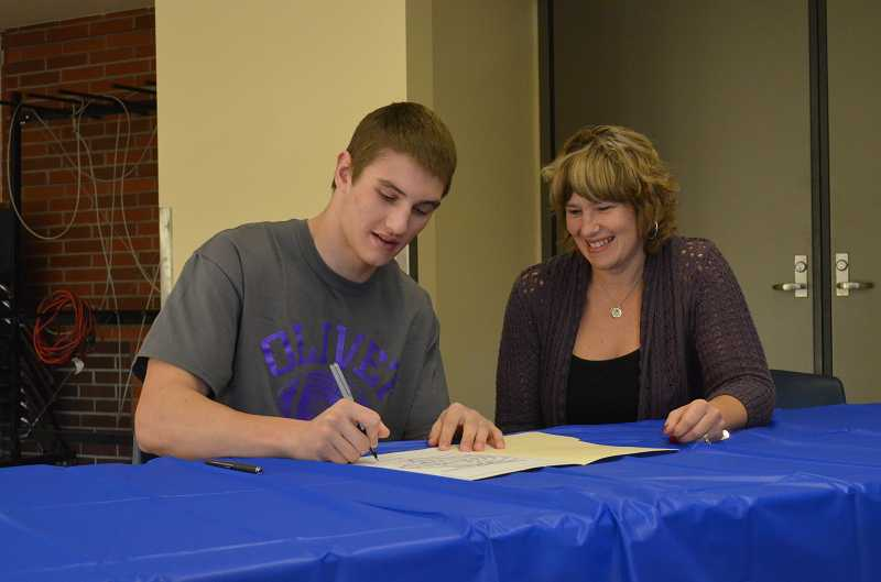 by: JEFF GOODMAN / PAMPLIN MEDIA GROUP - Steven Sawyer (left), shown with his mother, Bonnie, signs a letter of intent Feb. 5 at Wilsonville High School. The senior will continue his football career at Olivet Nazarene University in Illinois.