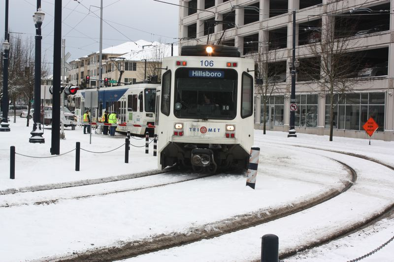 by: HILLSBORO TRIBUNE PHOTO: DOUG BURKHARDT - Snow and ice plagued TriMet during the storm. Snow clogged automatic switches essential to the operation of the light rail system, so maintenance crews were required to manually throw the switches around the network. On Friday, TriMet workers were assisting this MAX train coming into the Hatfield Transit Center in downtown Hillsboro.