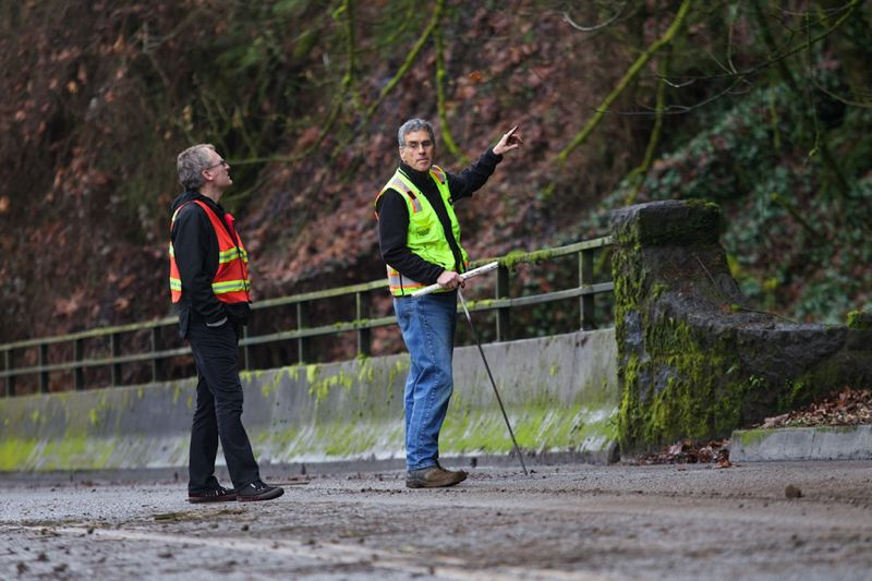 by: TRIBUNE PHOTO: JAIME VALDEZ - David O'Longaigh, left, and geologist Jim Wood survey the damage from a Friday morning landslide along Northwest Cornell Road.
